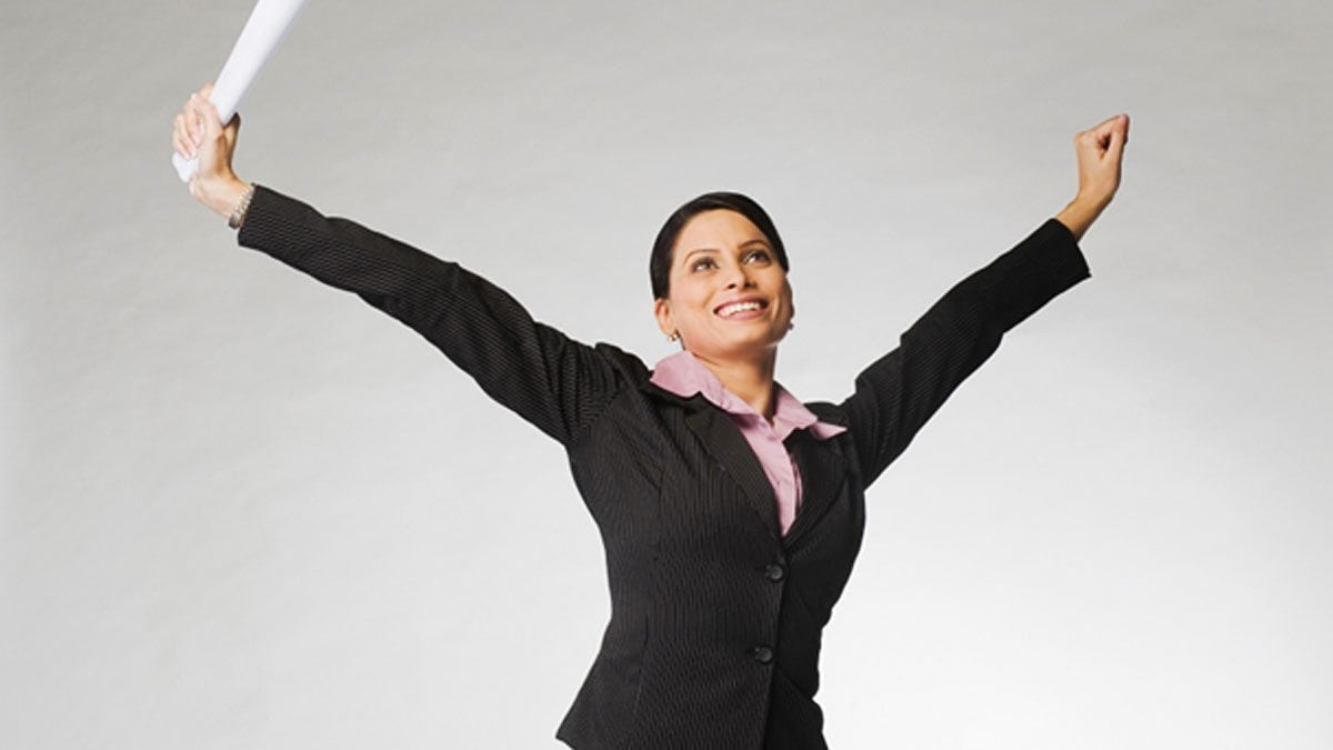 A business school graduate stands in the popular victory power pose.